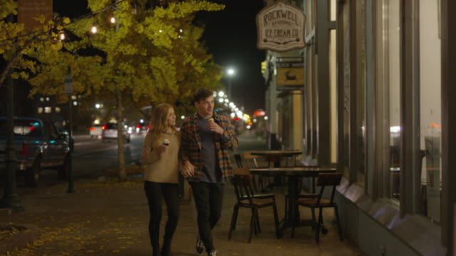 stockvideo's en b-roll-footage met wide to medium shot of couple on sidewalk eating ice cream cones / provo, utah, united states - provo