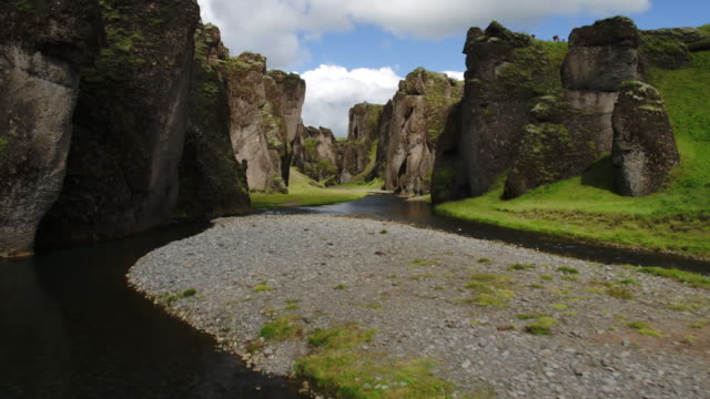 wide tracking flyover shot of river in canyon / iceland - canyon stock videos and b-roll footage