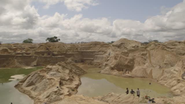 wide tracking shot of a man walking into a diamond mine pit in sierra leone. - sierra leone stock videos & royalty-free footage
