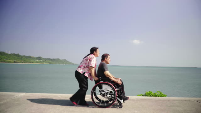vídeos de stock, filmes e b-roll de wide tracking shot of a senior woman taking her husband, who is in a wheelchair, for a walk in a park - assistência