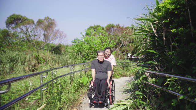 wide tracking shot of a senior woman taking her husband, who is in a wheelchair, for a walk in a park - 老化点の映像素材/bロール