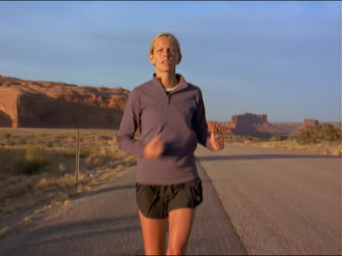 wide tracking shot of a young blonde female jogger as she runs down the side of the road - 女性ランナー点の映像素材/bロール