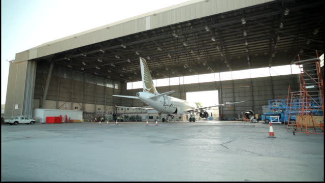 wide tracking shot of an airplane in a hangar at bahrain international airport. - airplane hangar stock videos & royalty-free footage