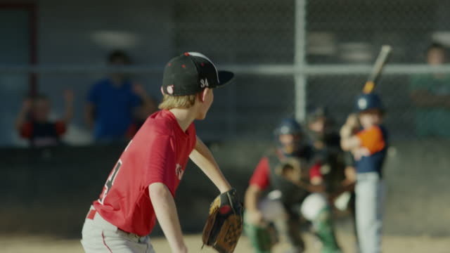 wide tracking shot of baseball batter hitting ball and running / american fork, utah, united states - hitting stock videos & royalty-free footage