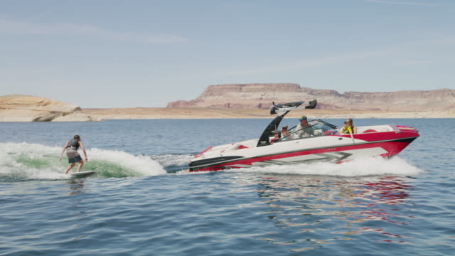 vídeos de stock e filmes b-roll de wide tracking shot of boat pulling wake surfer / lake powell, utah, united states - lago powell