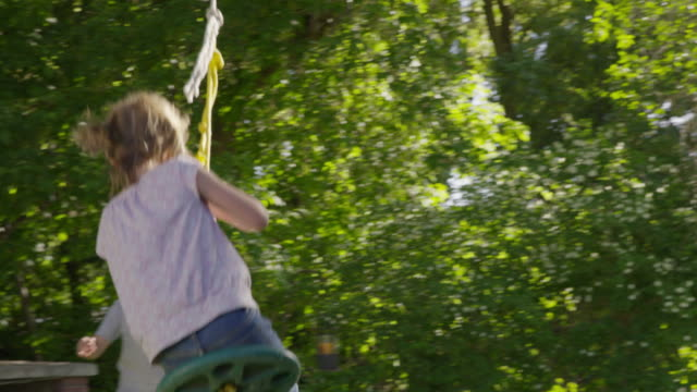 wide tracking shot of boy pushing girl on rope swing / springville, utah, united states - springville utah stock-videos und b-roll-filmmaterial