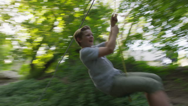 wide tracking shot of boy swinging on rope swing / springville, utah, united states - springville utah stock videos & royalty-free footage