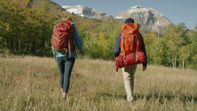 Wide tracking shot of couple hiking near mountain / American Fork Canyon, Utah, United States