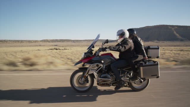 Wide tracking shot of couple riding motorcycle on desert road / Ferron, Utah, United States