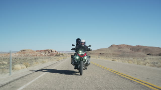 wide tracking shot of couple riding motorcycle on desert road / ferron, utah, united states - approaching stock videos & royalty-free footage