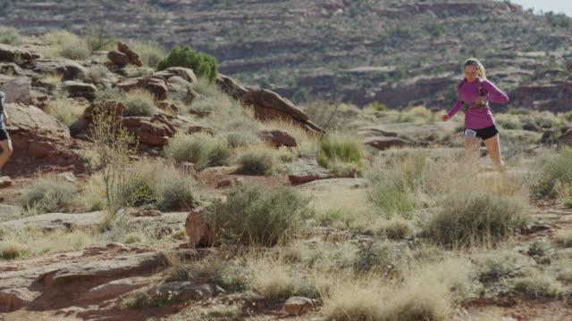 vídeos de stock, filmes e b-roll de wide tracking shot of couple trail running in desert / moab, utah, united states - calções de corrida