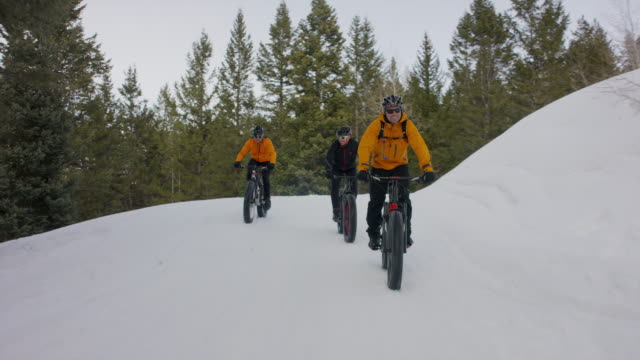 wide tracking shot of friends riding fat bikes on mountain / american fork canyon, utah, united states - american fork canyon bildbanksvideor och videomaterial från bakom kulisserna