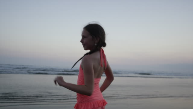 """Wide tracking shot of girl dancing on beach / Esterillos, Puntarenas, Costa Rica"""