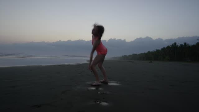 """wide tracking shot of girl doing cartwheel on beach / esterillos, puntarenas, costa rica"" - puntarenas stock-videos und b-roll-filmmaterial"