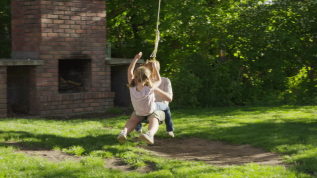 wide tracking shot of girl on lap of boy on rope swing / springville, utah, united states - springville utah stock-videos und b-roll-filmmaterial