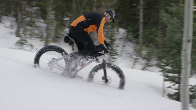 wide tracking shot of man falling from fat bike in forest / american fork canyon, utah, united states - american fork canyon stock videos and b-roll footage