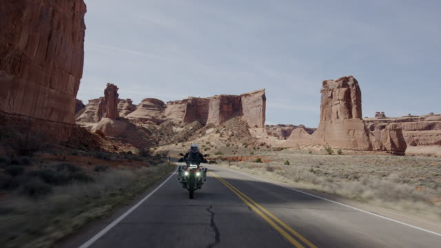 stockvideo's en b-roll-footage met wide tracking shot of man riding motorcycle on desert road / arches national park, utah, united states - dichterbij komen