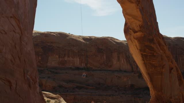 vídeos y material grabado en eventos de stock de wide tracking shot of man swinging from arch / corona arch, moab, utah, united states - puenting