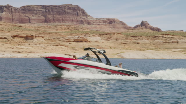 vídeos de stock e filmes b-roll de wide tracking shot of people in speedboat on lake / lake powell, utah, united states - lago powell