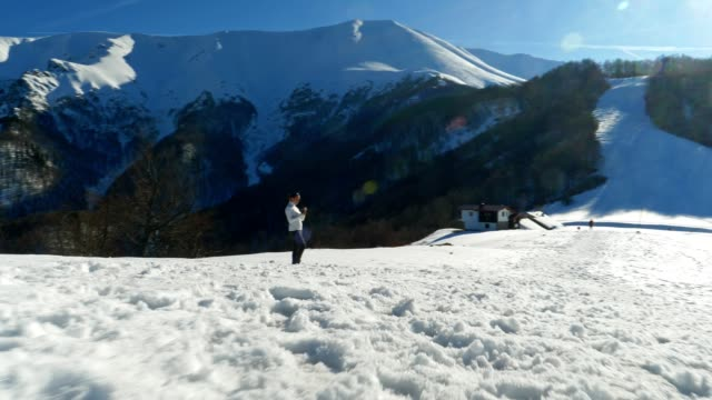 wide tracking shot of winter traveler at sunset using camera, close up of one young woman tourist taking photos, photographing, enjoying the winter mountain, portrait, winter sport, travel, exploration, adventure, tourism, outdoors, mountain hiking, - side lit stock videos & royalty-free footage
