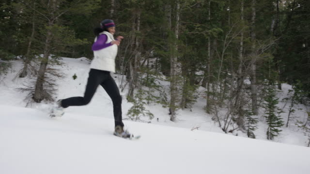 Wide tracking shot of woman running in snow shoes in forest / American Fork Canyon, Utah, United States