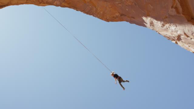 vídeos y material grabado en eventos de stock de wide tracking shot of woman swinging from arch / corona arch, moab, utah, united states - puenting