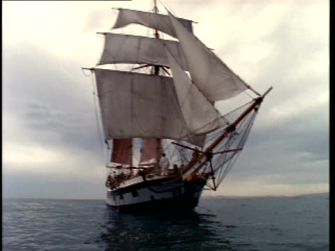 wide tracking shot toward large sailing ship on sea/ medium shot along side of boat - tall high stock videos and b-roll footage