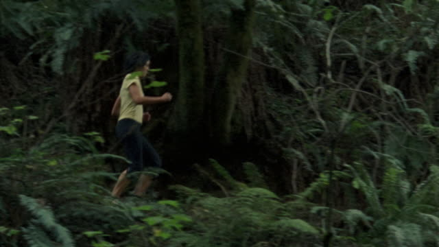 wide tracking shot woman running through forest/ california - only mature women stock videos & royalty-free footage