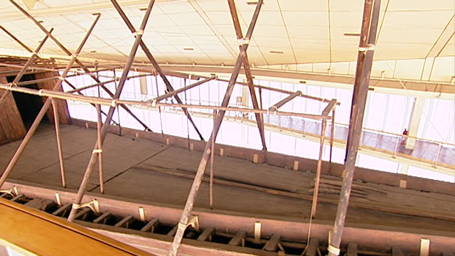 vídeos y material grabado en eventos de stock de wide tracking-left with egyptologist and author david rohl walking in the giza solar boat museum. built near the great pyramid the museum houses the... - barcaza embarcación industrial