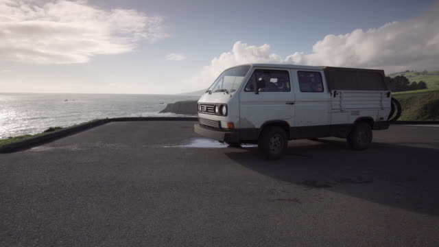 Wide, van drives along cliffside road