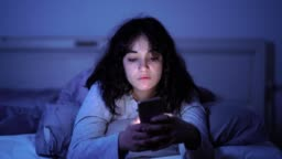 4K wide video of an Addicted young woman chatting and surfing on the internet using her smart phone sleepy, bored and tired late at night. Dramatic dark light. In Internet, Mobile addiction and insomnia concept.