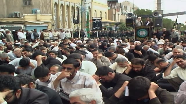 stockvideo's en b-roll-footage met wide view across shia clerics and men crouching and listening to a lamentation on a loudspeaker, at a funerary rite outside the fatima masumeh shrine. - hoofdtooi