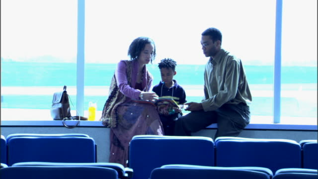 Wide view of a family waiting for their flight near a window.