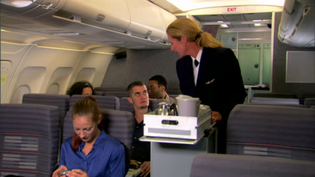 wide view of a flight attendant pushing her cart up the aisle to serve passengers snacks and drinks. - crew stock videos & royalty-free footage