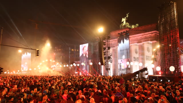 wide view of a performance of a music band by red light and of a projection on big screen of rapping singers on a big stage at the back of the... - brandenburg gate stock videos & royalty-free footage
