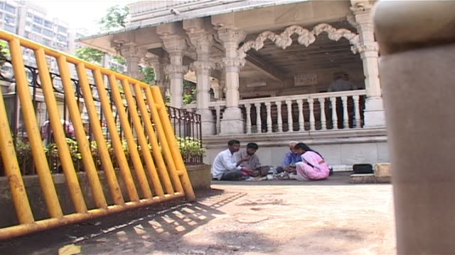 wide view of an indian family having a picnic in the courtyard of a hindu temple in the city. - indian ethnicity点の映像素材/bロール