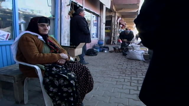wide view of an old woman sitting outside a shop in the market in midyat. - winter stock videos & royalty-free footage