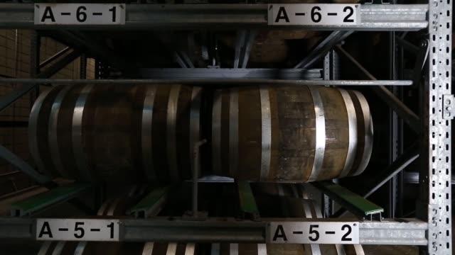 stockvideo's en b-roll-footage met wide view of barrels stacked on shelves inside the warehouse medium slider view of barrels stacked on shelves from top to bottom tilt up from bottom... - middelenmisbruik