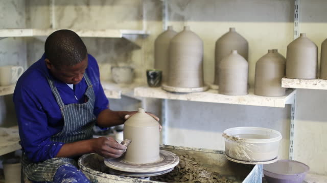 wide view of black male potter using his hands to make clay vases - ceramics stock videos & royalty-free footage