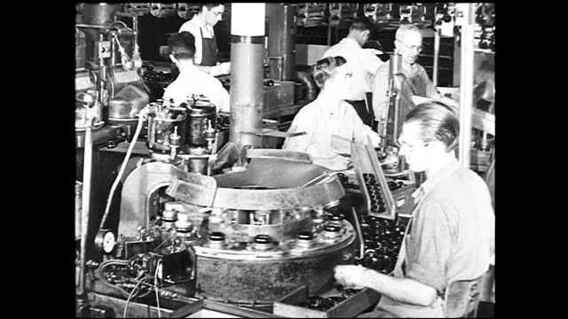 vidéos et rushes de wide view of busy factory full of workers sitting down and working; workers sitting around the assembly table; two workers working on press machine,... - 1940 1949