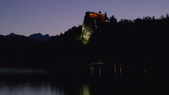Wide view of castle on hill at night / Bled, Slovenia