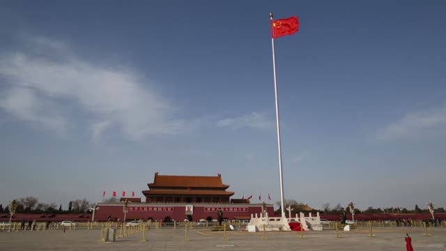 vídeos de stock, filmes e b-roll de wide view of chinese national flag fluttering at the top of a flag pole at tiananmen gate in beijing china on monday march 2 2015 - portão da paz celestial de tiananmen