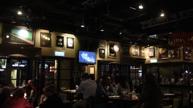 wide view of customers seated inside the restaurant of the hard rock cafe hong kong operated by hard rock international inc in the lan kwai fong area... - hard rock cafe stock videos & royalty-free footage