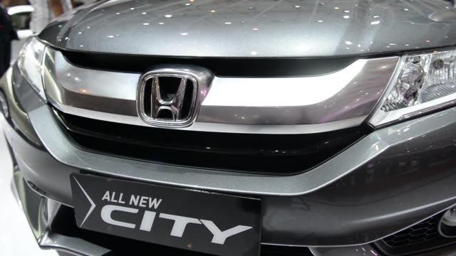 wide view of exhibitions and honda logo and attendees looking at vehicles on display during the indonesia international motor show in jakarta... - honda stock videos & royalty-free footage