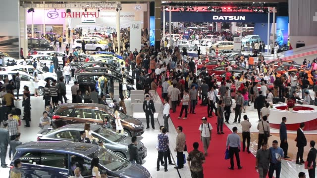 wide view of exhibitions and honda logo and attendees looking at vehicles on display during the indonesia international motor show in jakarta... - trade show booth stock videos & royalty-free footage