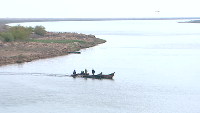 wide view of fishermen leaving the shore of shatt al-arab in a motorboat. the river is formed by the confluence of the euphrates and tigris and runs... - basra stock-videos und b-roll-filmmaterial