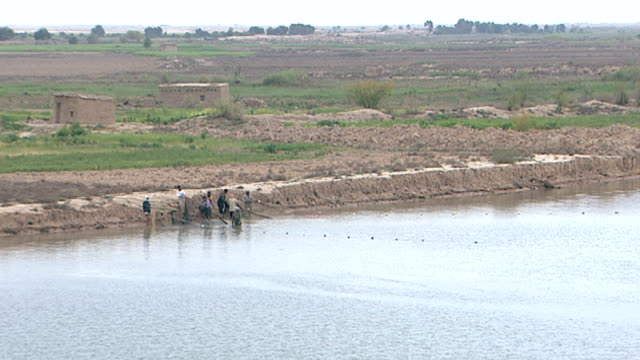 wide view of fishermen on the bank of shatt al-arab pulling on a net. the river is formed by the confluence of the euphrates and tigris and runs into... - basra video stock e b–roll