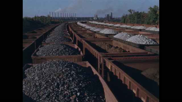 wide view of hundreds of rail cars filled with iron ore and other materials delivered to steel plant - eisenerz stock-videos und b-roll-filmmaterial