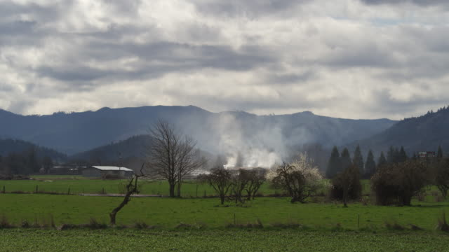 Wide view of rural fields with mountains in background; smoke rising from a burning house in distance