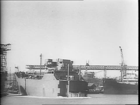 Wide view of shipyard / tanker at a shipyard / person christening the ship / ship pulling out of the yard / half of a tanker ship launching in to the...